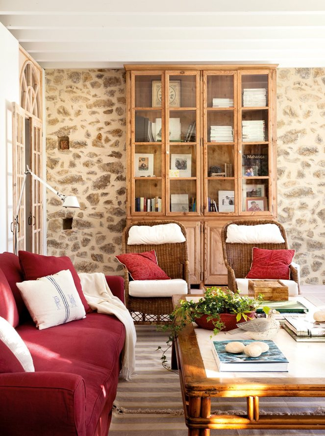 salon_con_pared_de_piedra_libreria_antigua_y_sofa_rojo_953x1280