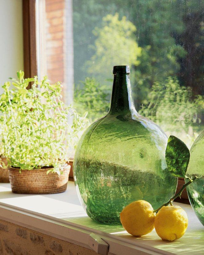 detalle_de_botella_de_cristal_planta_y_limones_sobre_repisa_de_la_ventana_1024x1280